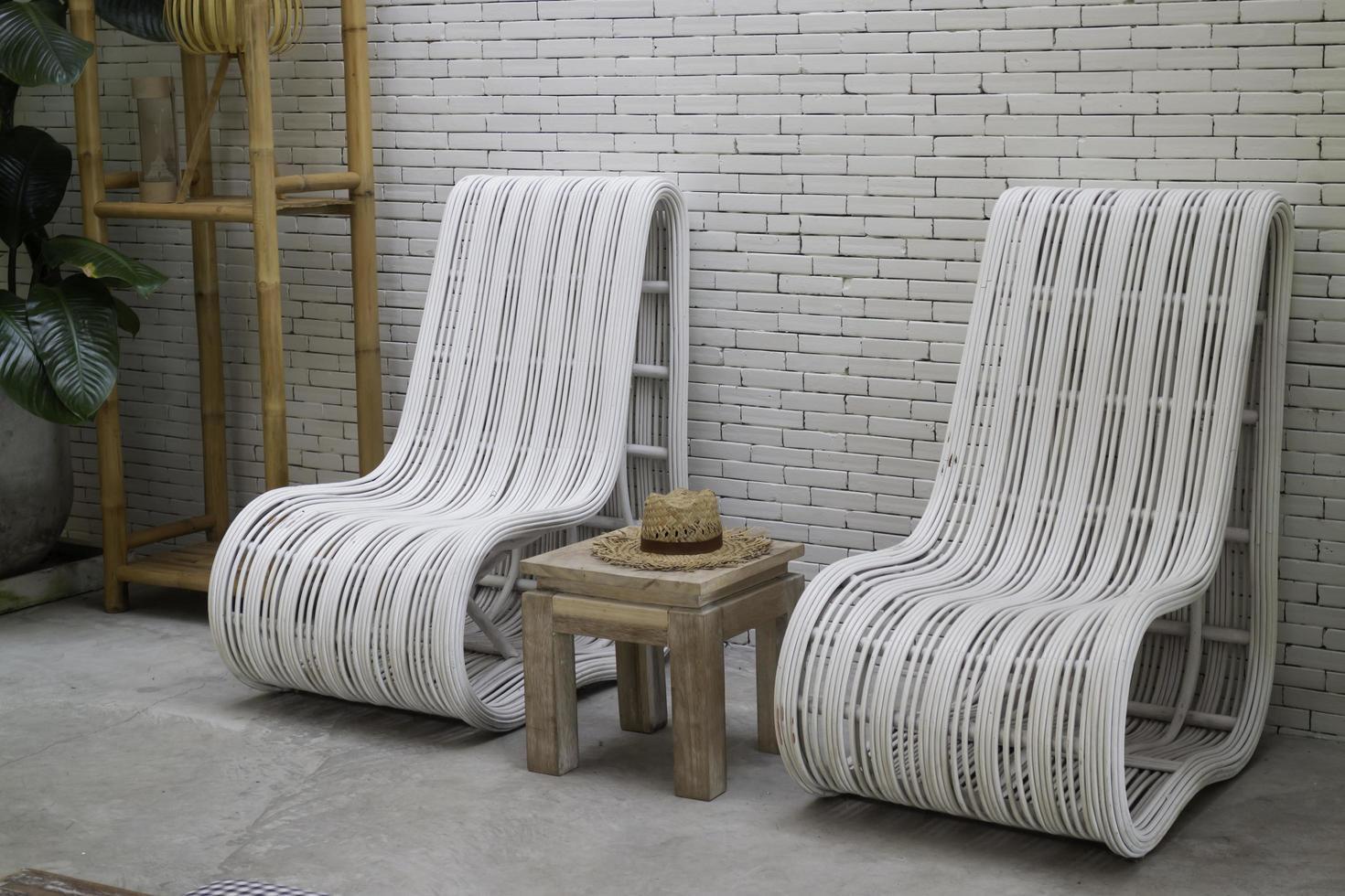Chaises blanches contre un mur de briques photo