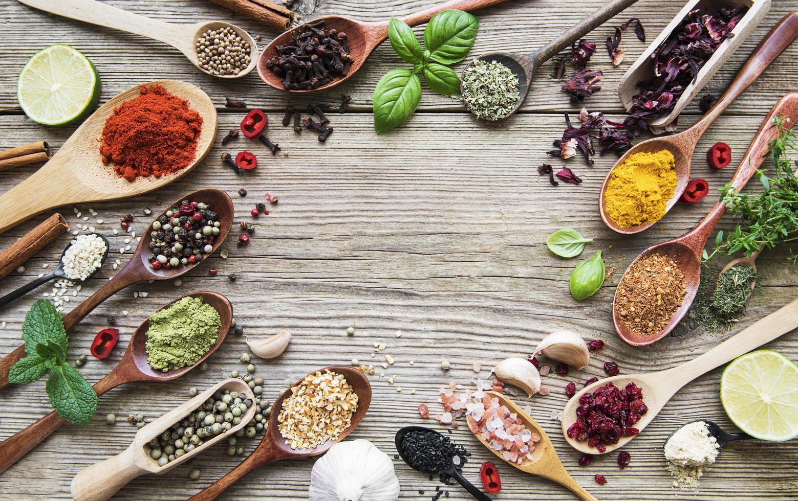une sélection de diverses épices colorées sur une table en bois dans des cuillères photo