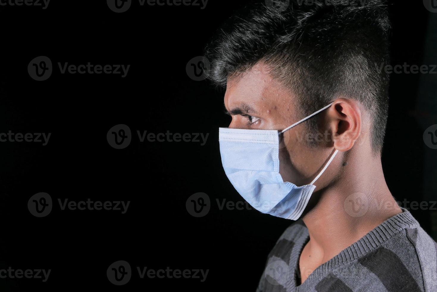 Profil de côté d'un homme portant un masque sur fond noir photo