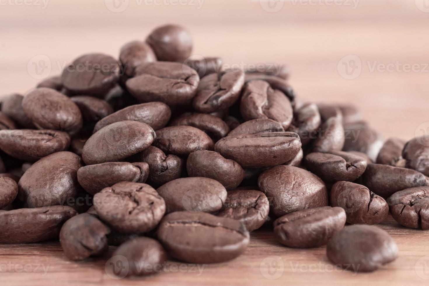 Gros plan d'un tas de grains de café frais sur bois photo