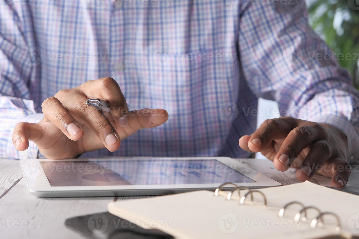 La main de l'homme travaillant sur une tablette numérique au bureau photo