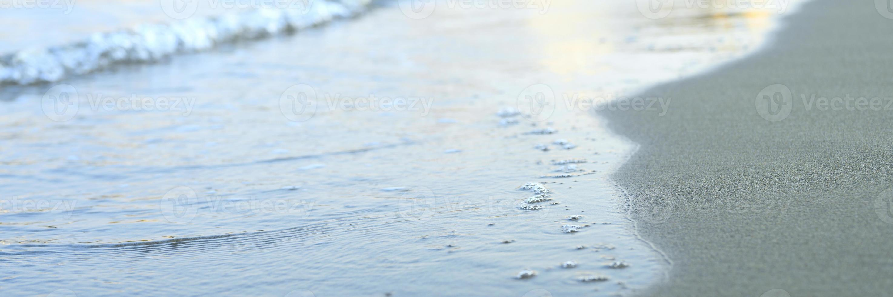 vague floue de la mer sur la plage de sable du soir photo