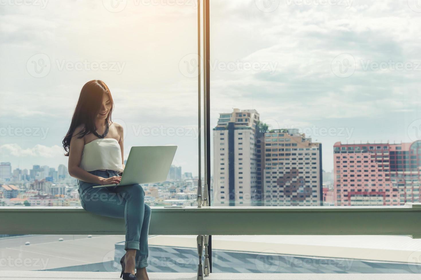 Femme à l'aide d'un ordinateur portable avec fond de paysage urbain photo