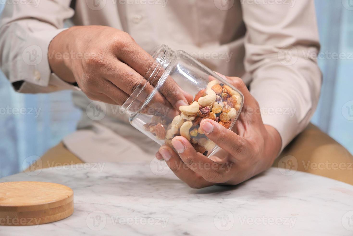 Homme mangeant des noix mélangées dans un pot photo