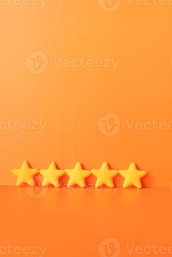cinq étoiles sur backgorund orange photo