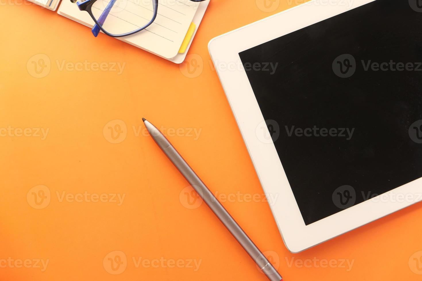 tablette numérique et stylet sur fond orange photo