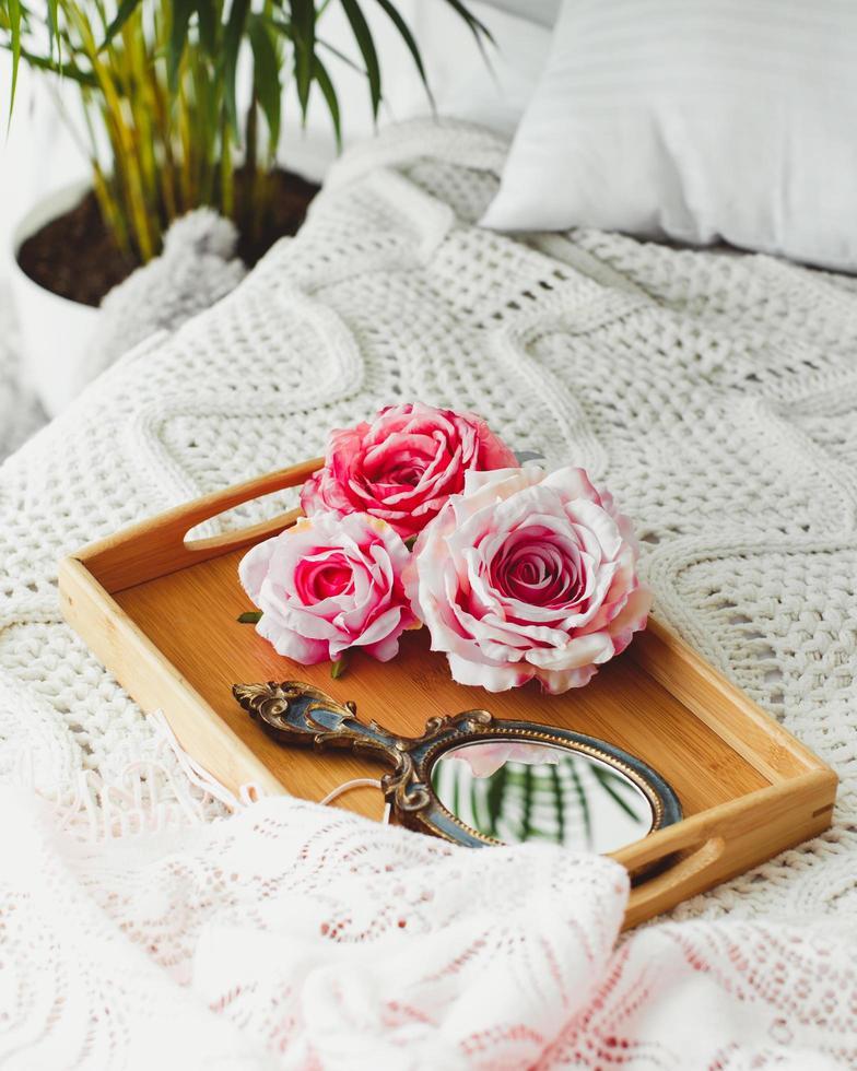plateau en bois avec miroir et roses roses mis sur une couverture tricotée photo