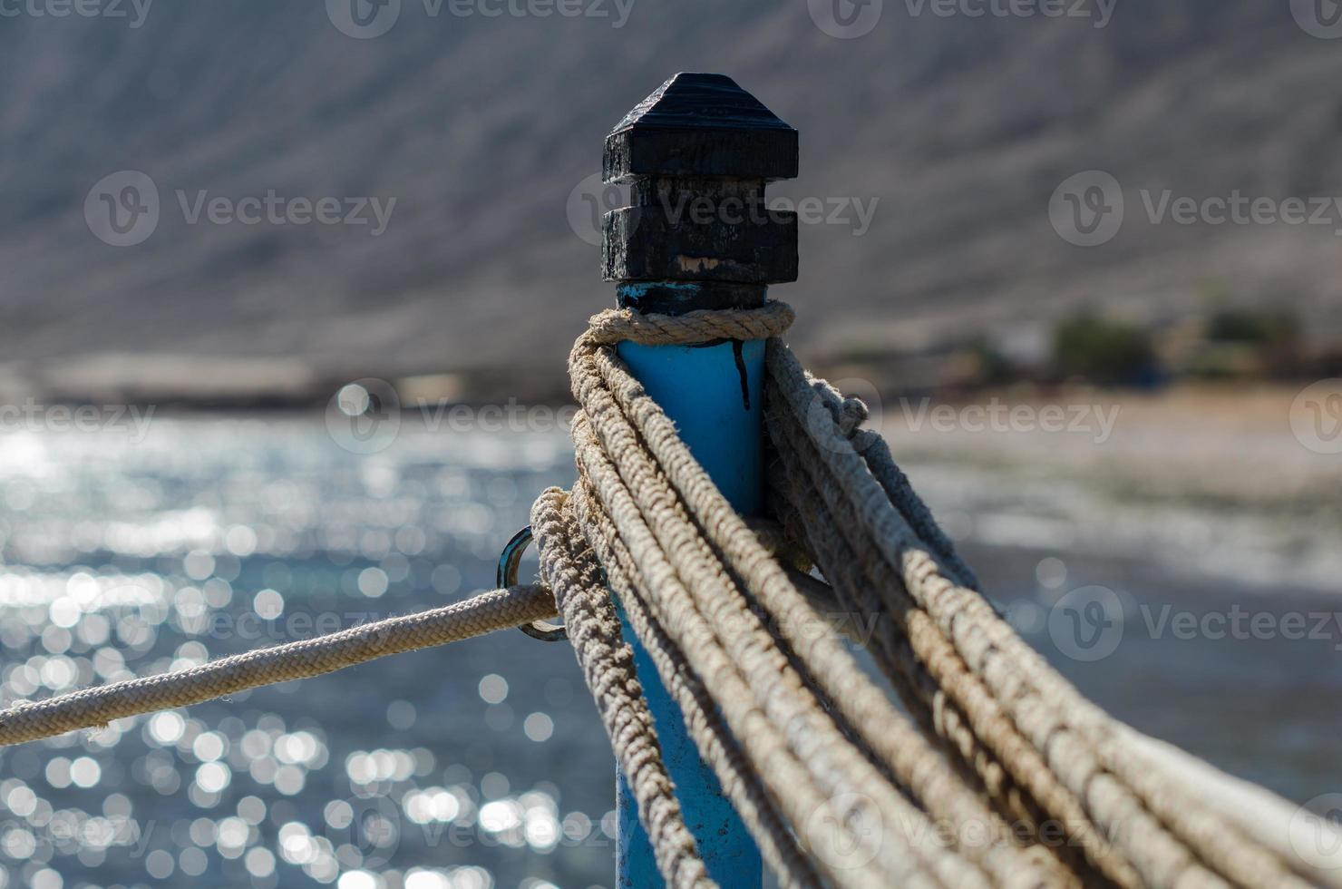 cordes sur un poteau contre la mer bleue photo
