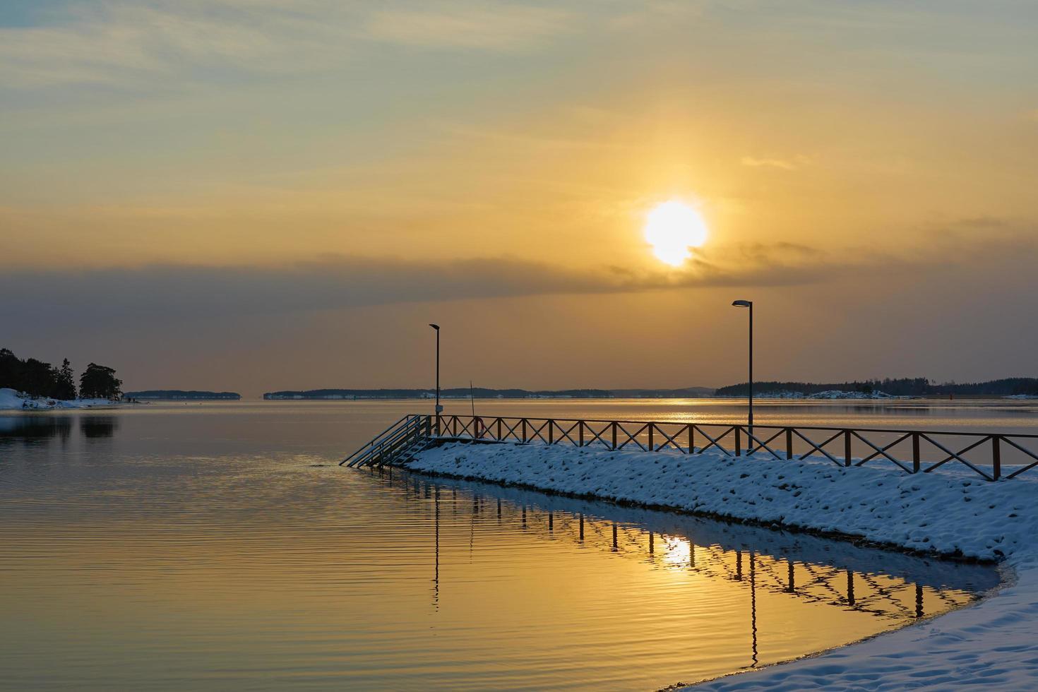 jetée couverte de neige au coucher du soleil au bord de la mer photo