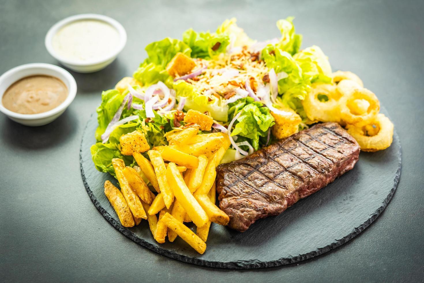 Steak de viande de bœuf grillé avec frites rondelle d'oignon avec sauce et légumes frais photo