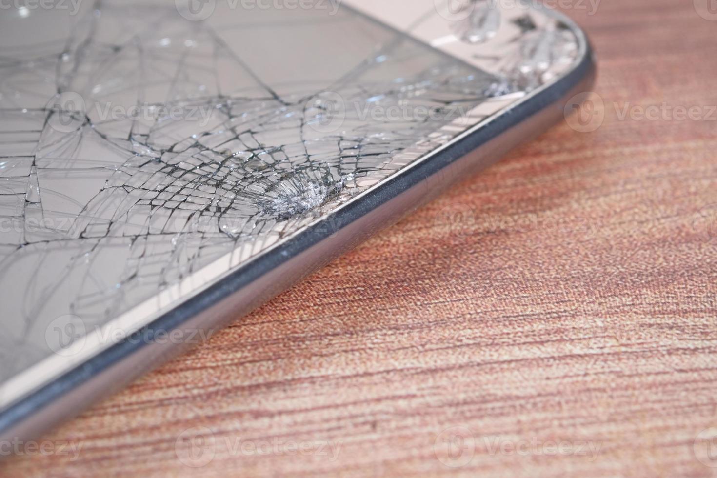 écran de téléphone intelligent cassé sur fond de bois photo