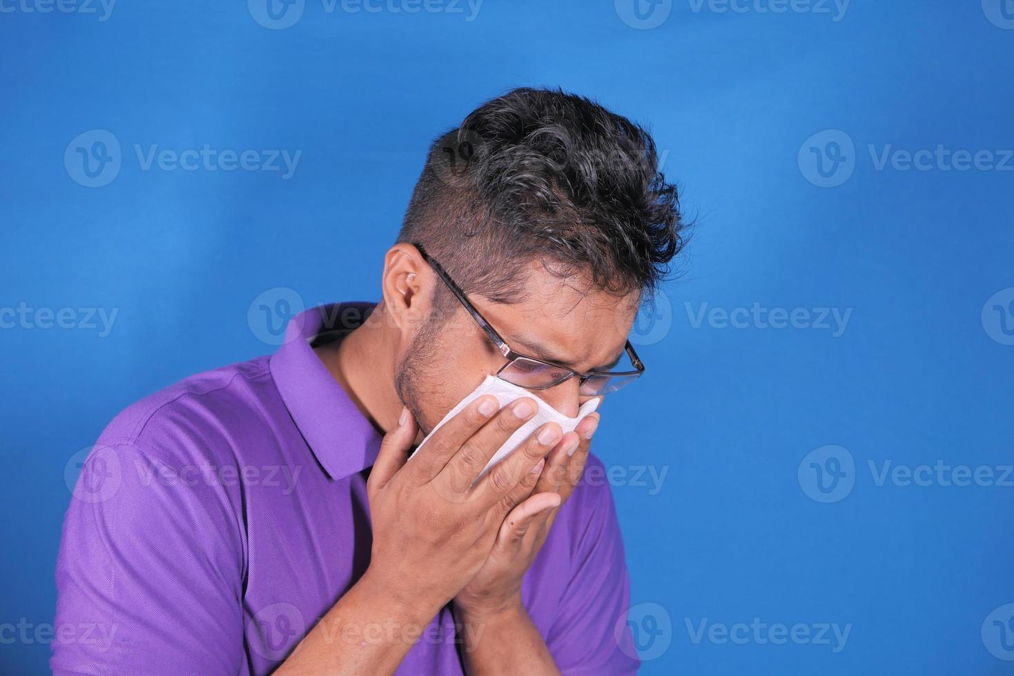 homme en chemise violette éternuements sur fond bleu photo