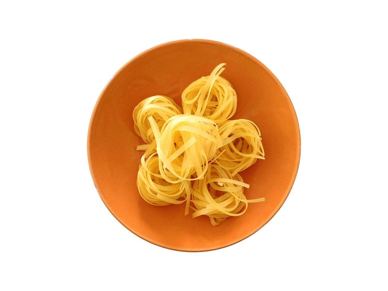 Pâtes dans un bol orange isolé sur fond blanc photo