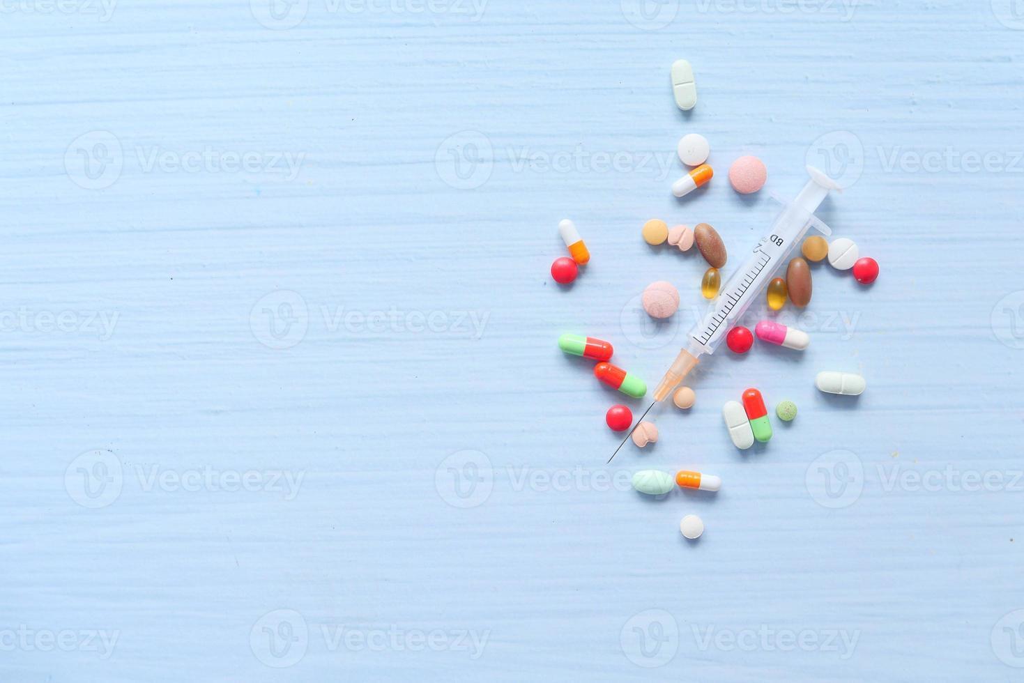 seringue et pilules sur fond blanc, vue du dessus photo