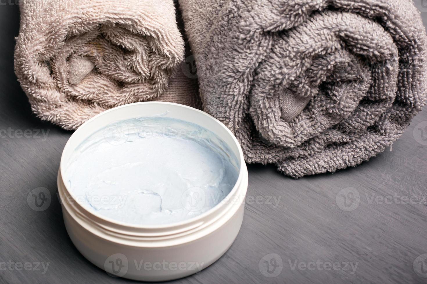 Serviettes roulées de couleur pastel et gommage corporel sur fond gris close-up photo
