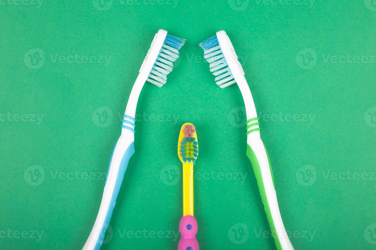 ensemble de brosses à dents pour toute la famille sur fond vert photo