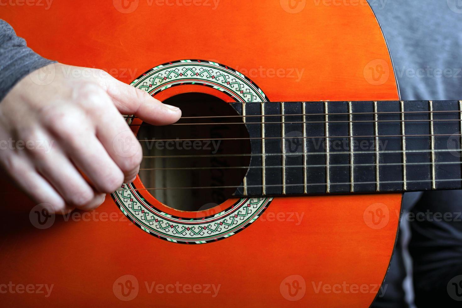 homme jouant avec guitare orange acoustique photo