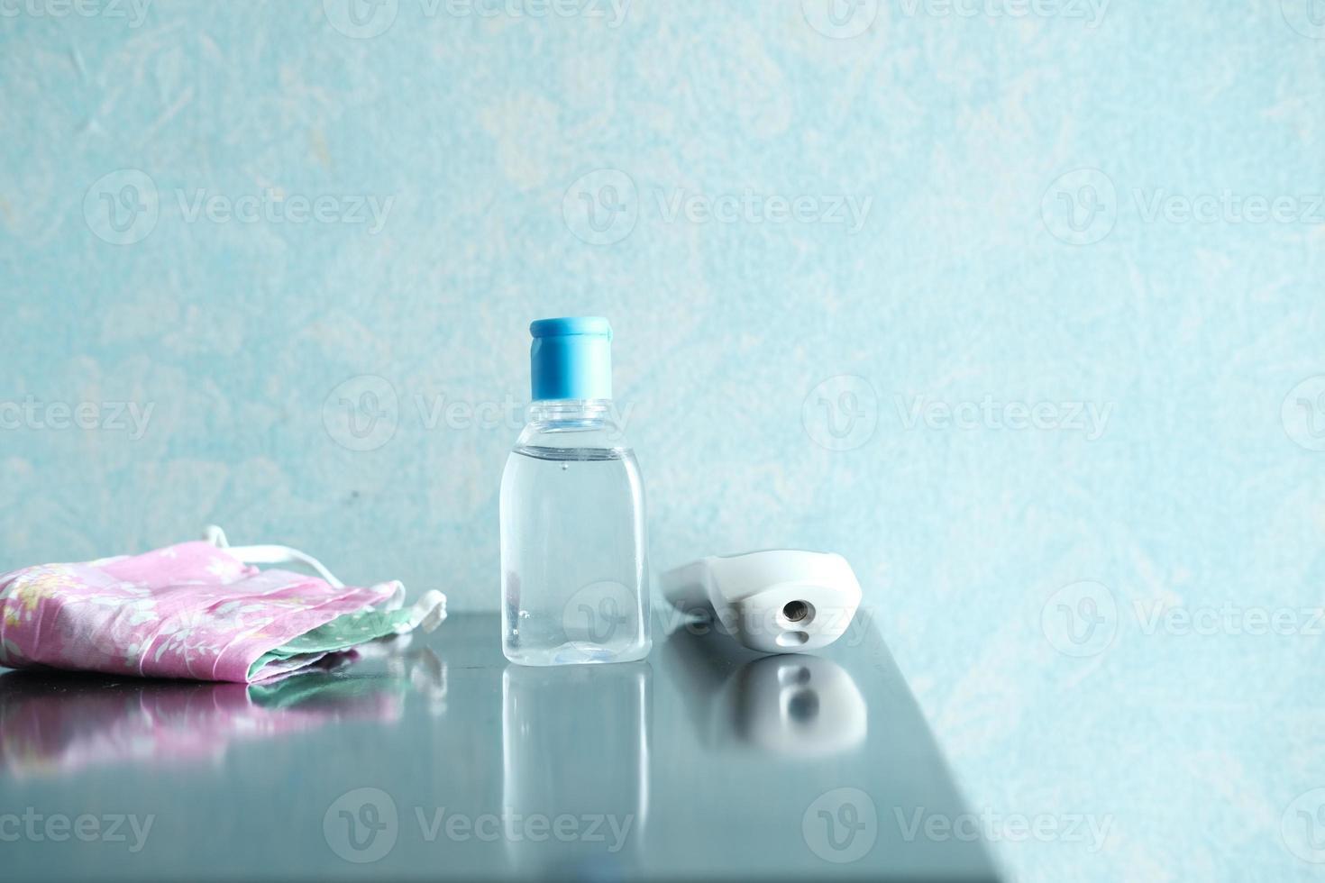 masques chirurgicaux, thermomètre et désinfectant pour les mains sur la table photo