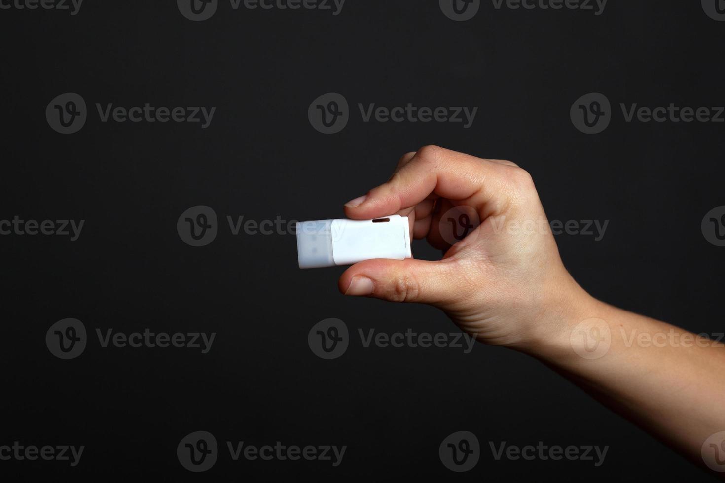 lecteur flash en main sur un fond noir foncé photo