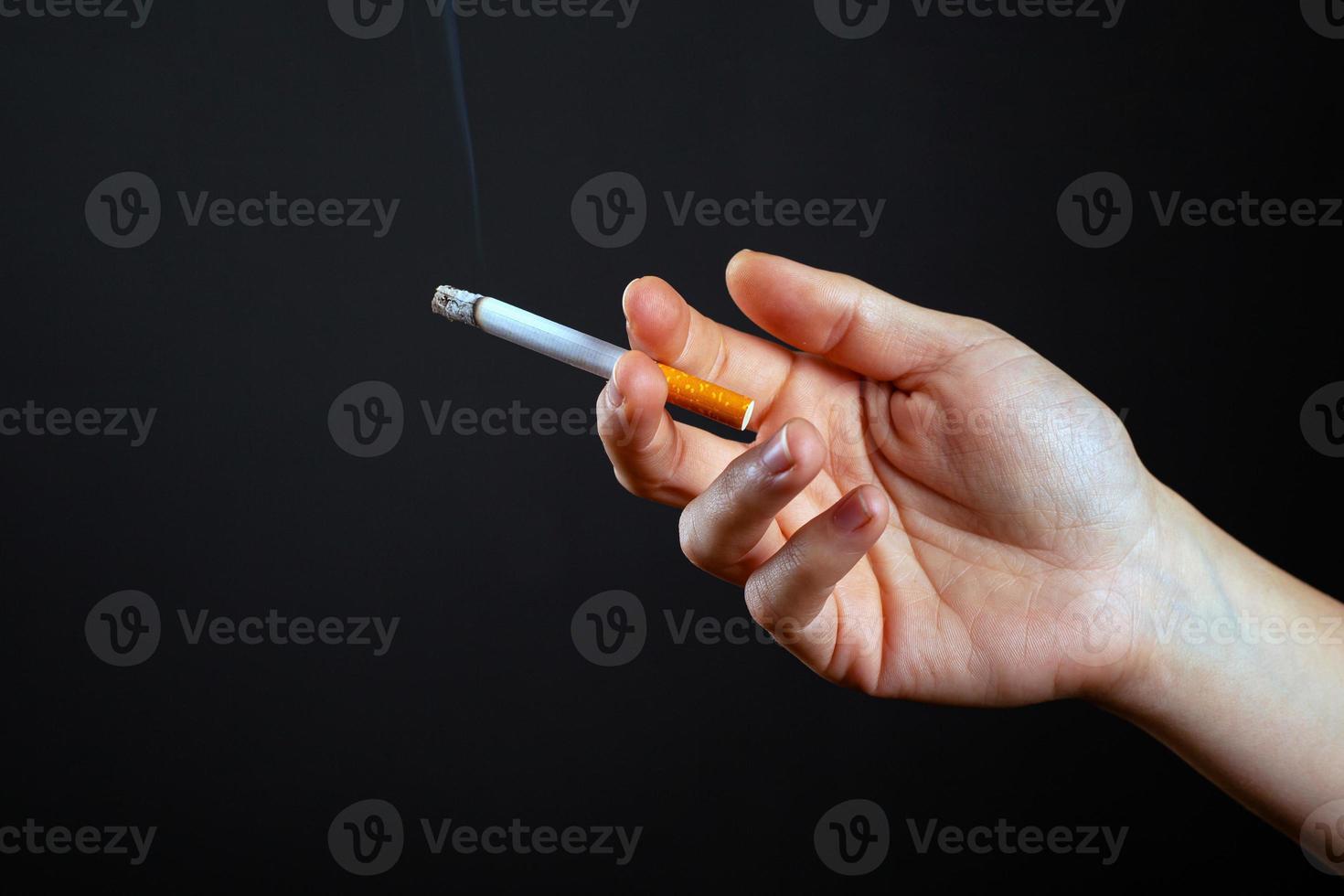 Main féminine tenant une cigarette sur un fond sombre photo