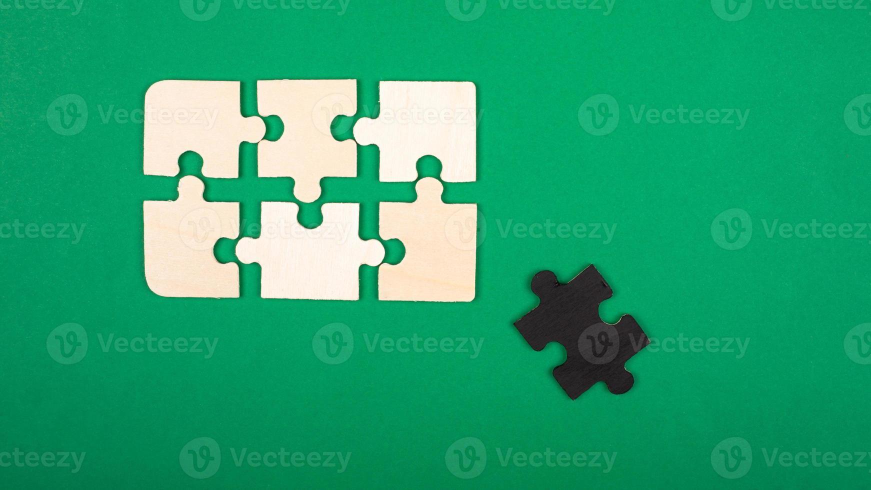 pièces du puzzle, couleurs blanc et noir sur fond vert photo