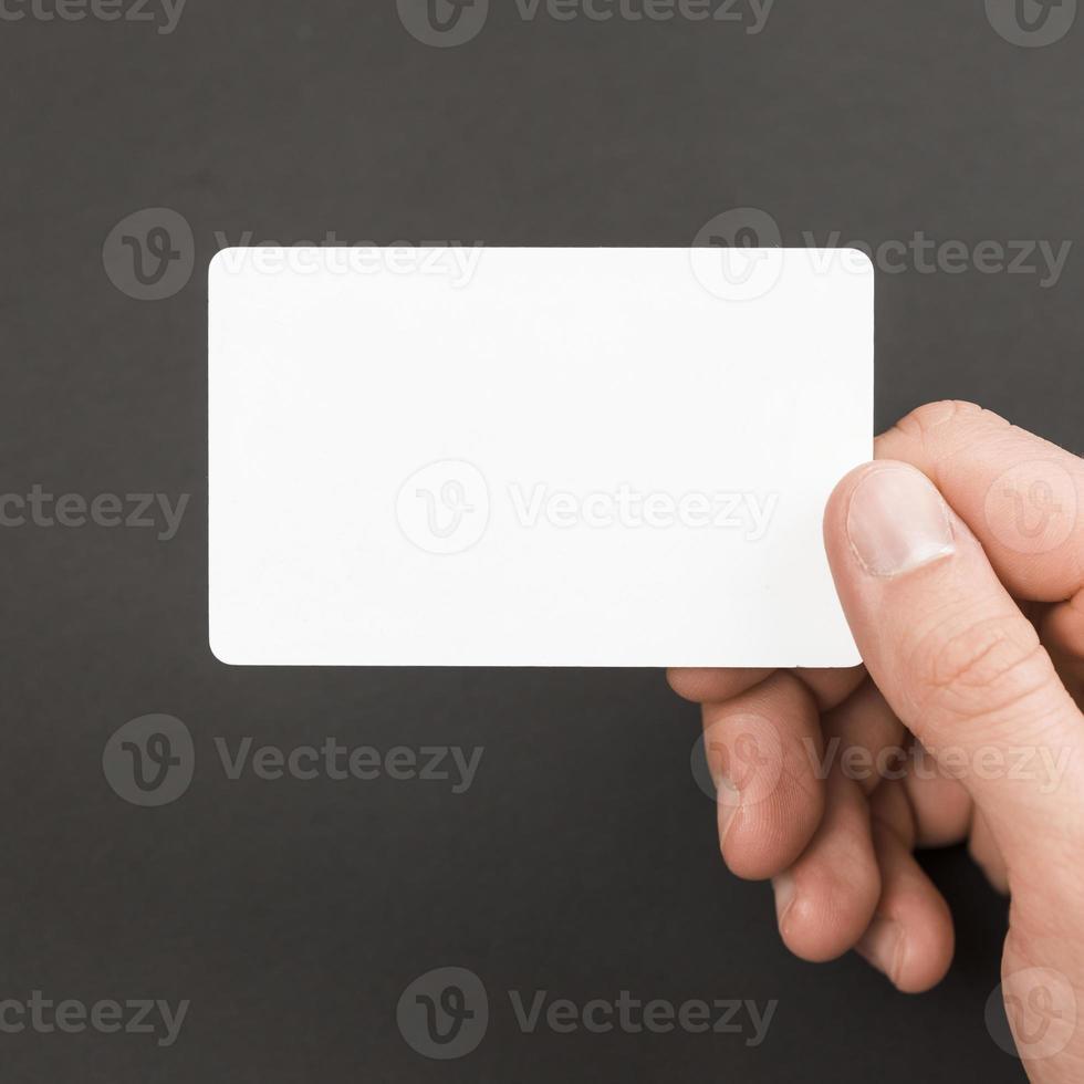 main tenant la carte de visite sur fond gris photo