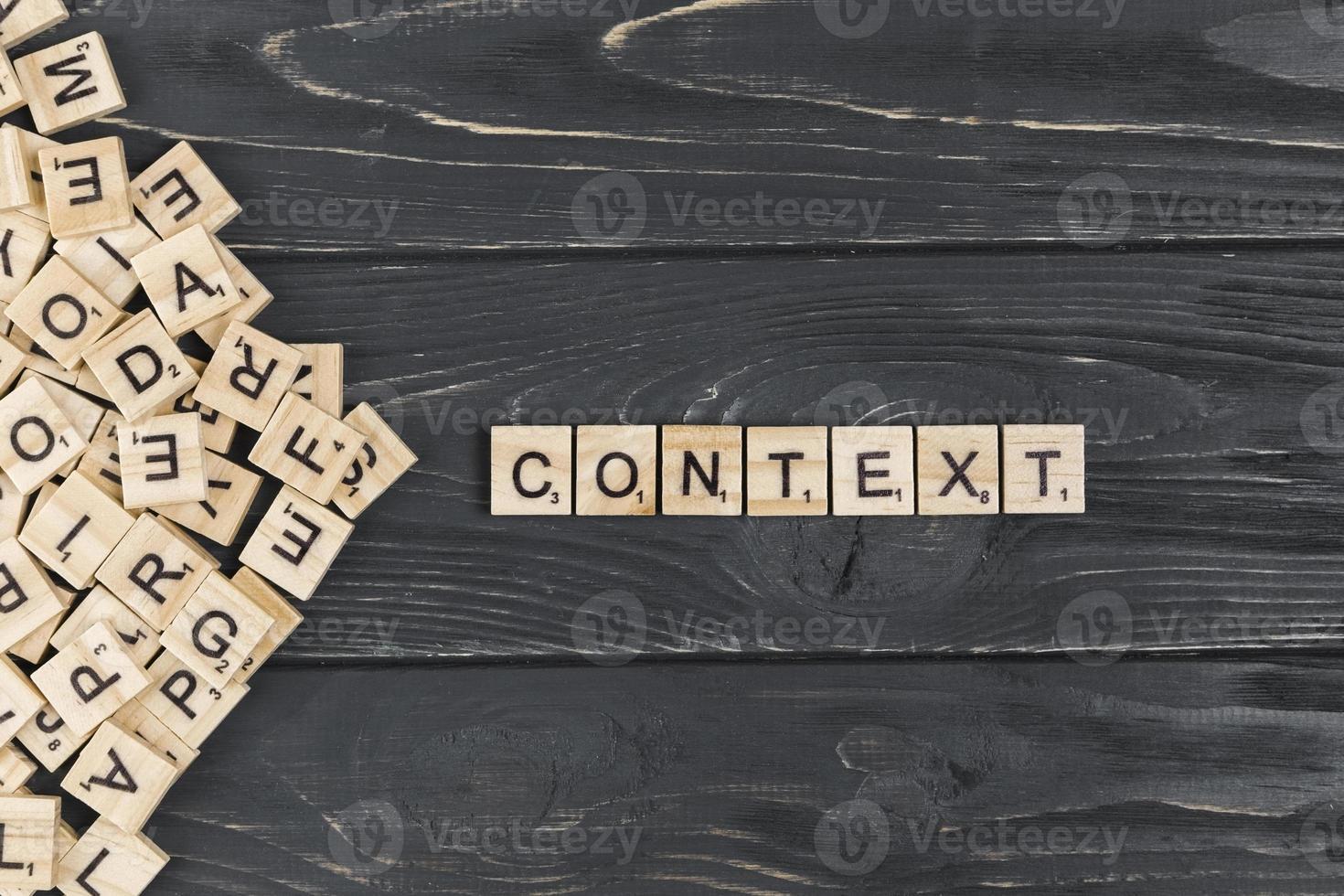 Mot de contexte sur des pièces en bois sur fond de bois foncé photo