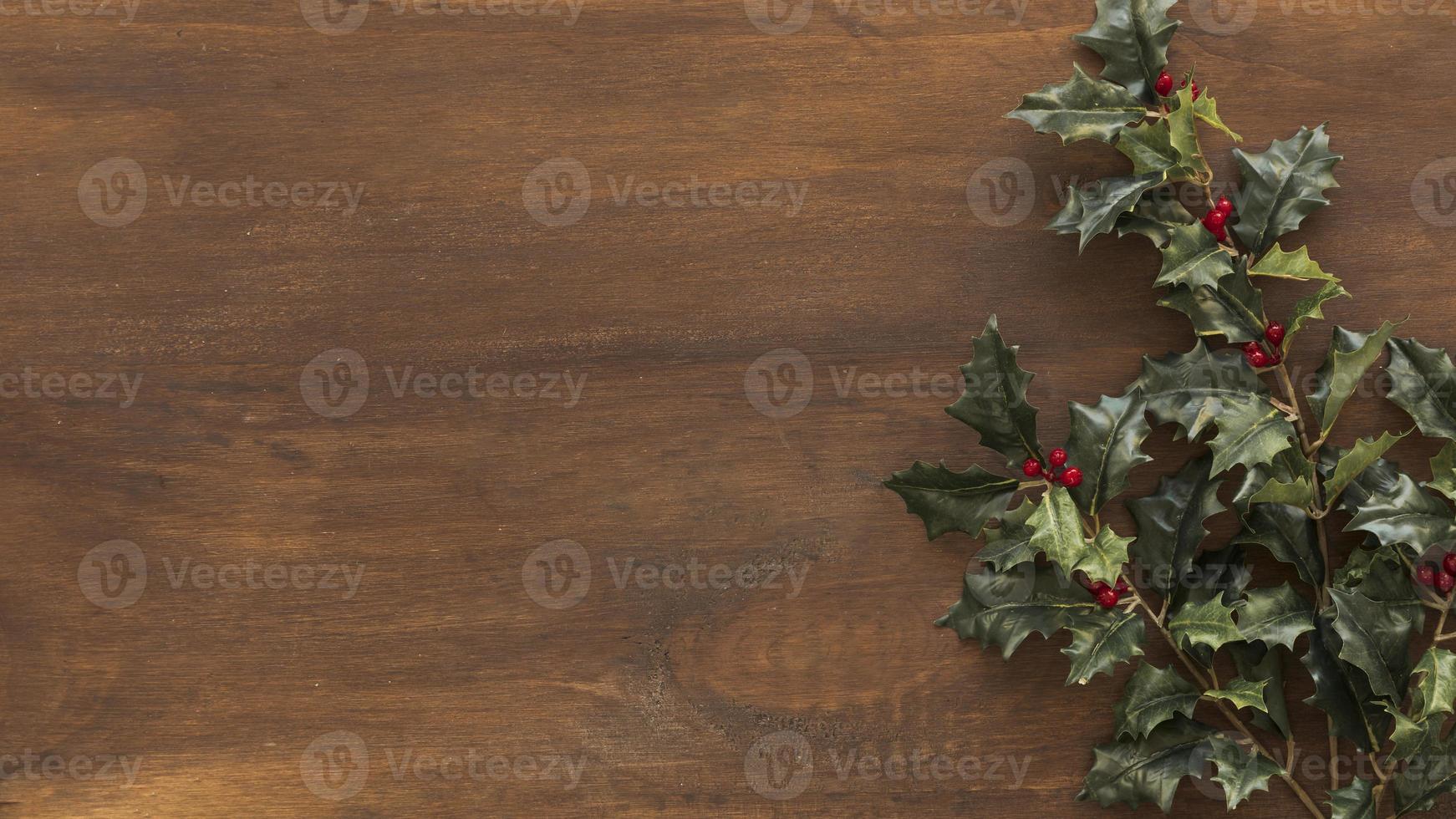 Branches de houx vert sur table marron photo