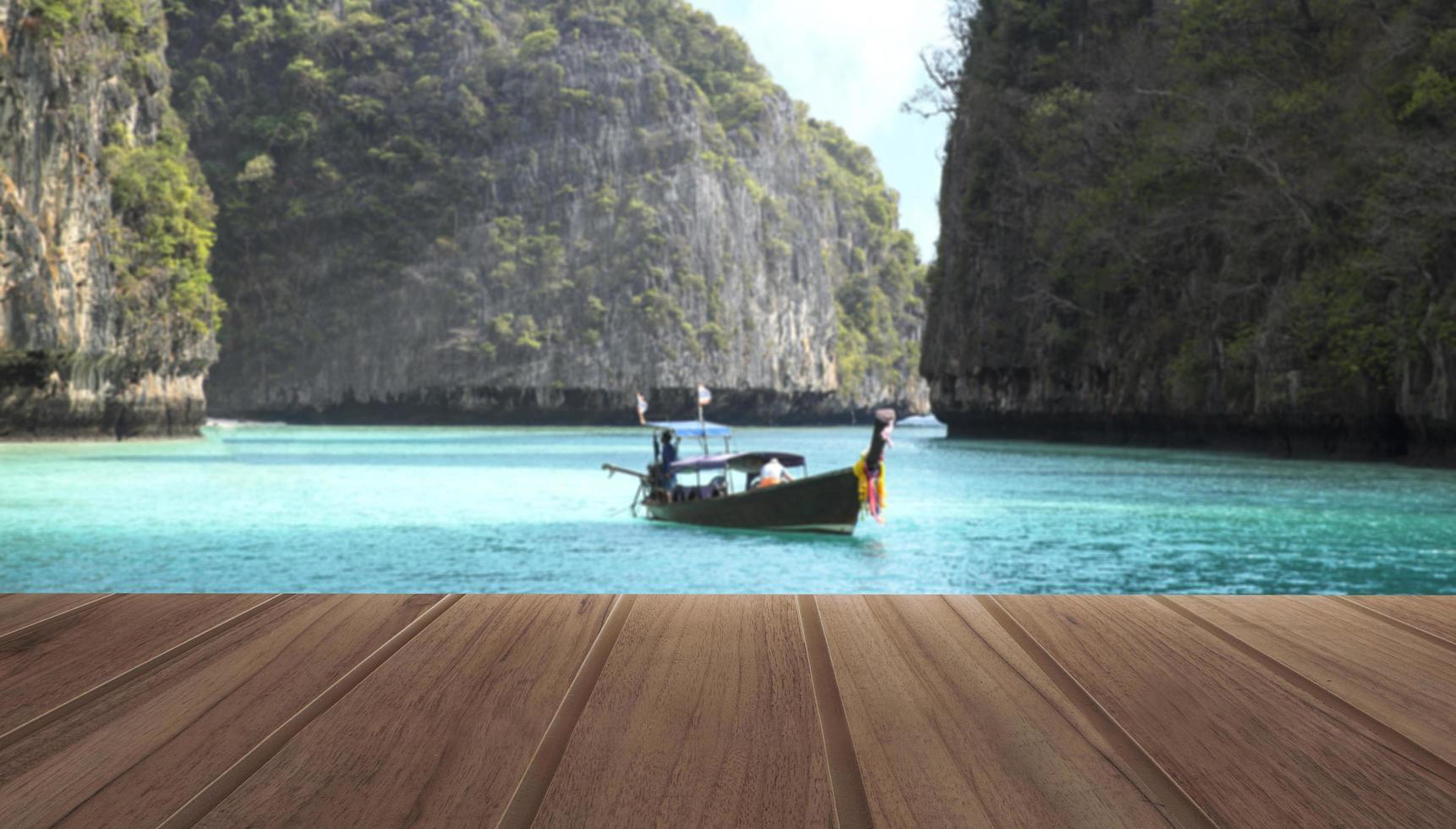 Table en bois sur la vue de dessus de la belle mer et bateau en bois avec des montagnes dans une station balnéaire tropicale pendant une journée d'été photo