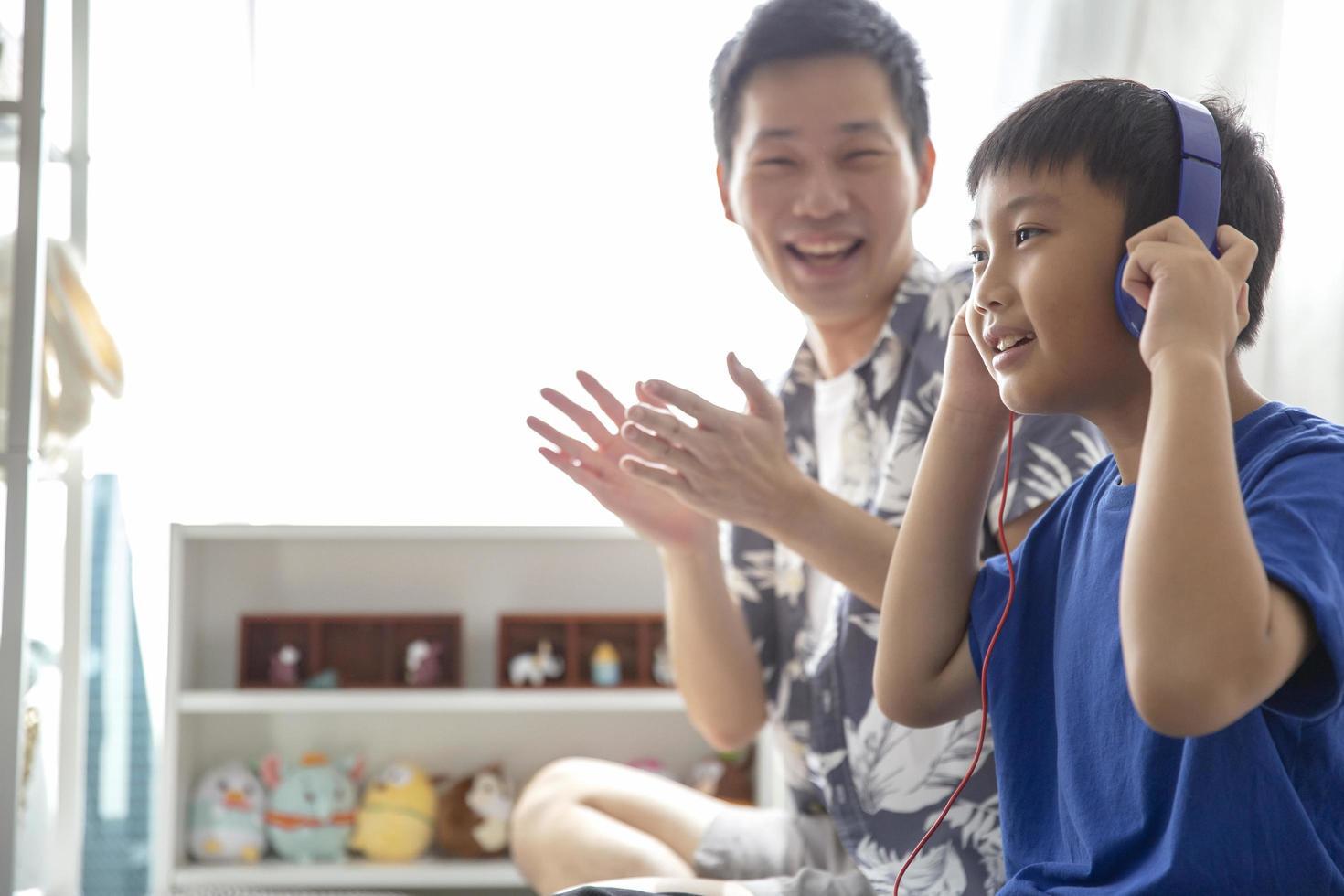 famille heureuse tout en utilisant des écouteurs pour écouter de la musique et sourire, profitez de passer du temps ensemble à la maison photo