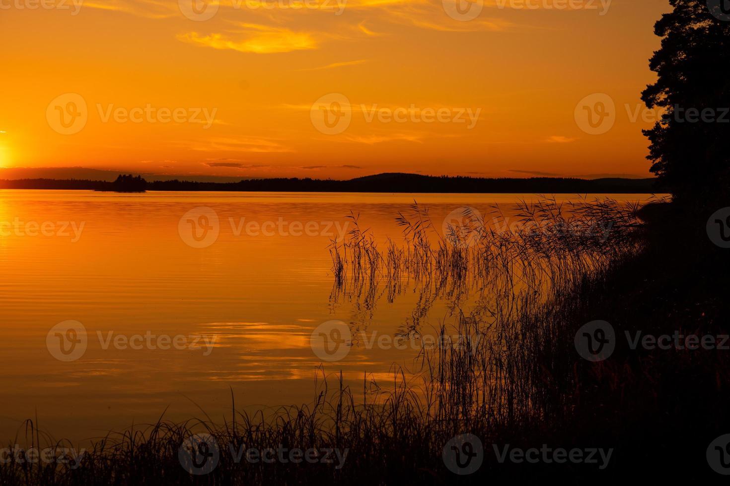 belle vue sur un lac avec la lumière du soleil orange brillant photo