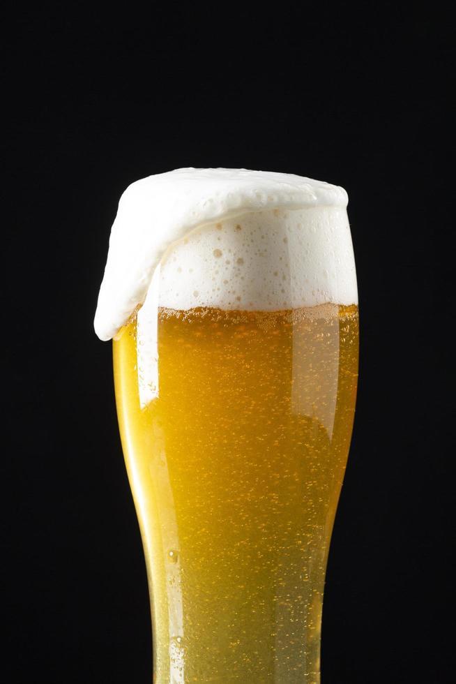 bière avec de la mousse sur fond noir photo