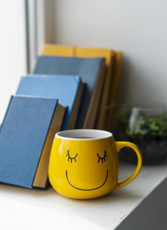 tasse de café jaune heureux avec des livres photo