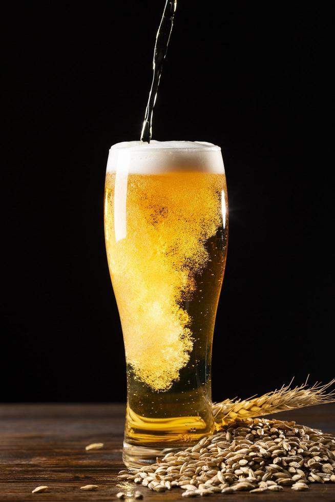 bière versée dans un verre sur fond noir photo