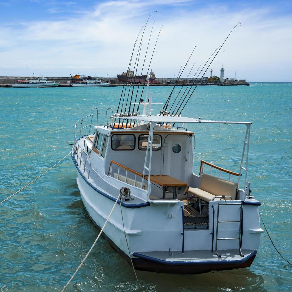 yacht blanc avec des cannes à pêche sur le fond du paysage marin photo