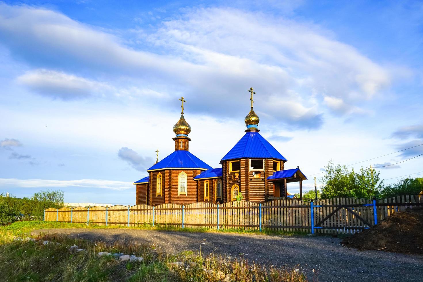 chapelle en bois au toit bleu au bord de la baie de kola. photo