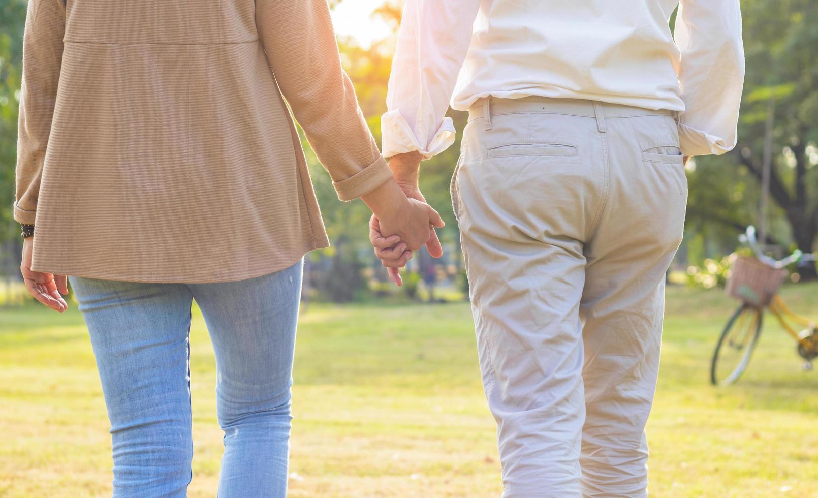 Couple de personnes âgées se tenir la main et se promener joyeusement dans le parc en vacances photo