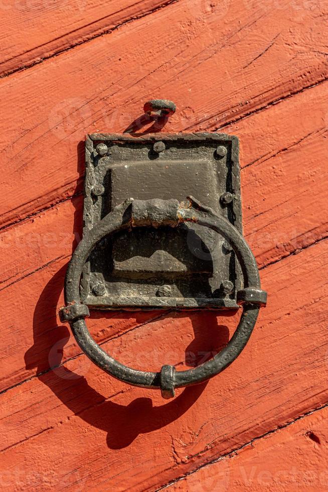 Ancien heurtoir de porte en fer sur une porte en bois rouge photo