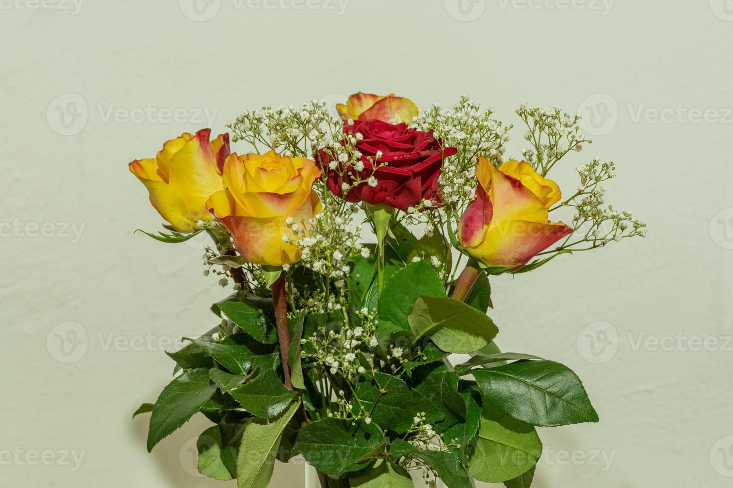 beau bouquet romantique de roses jaunes et rouges avec des feuilles vertes photo