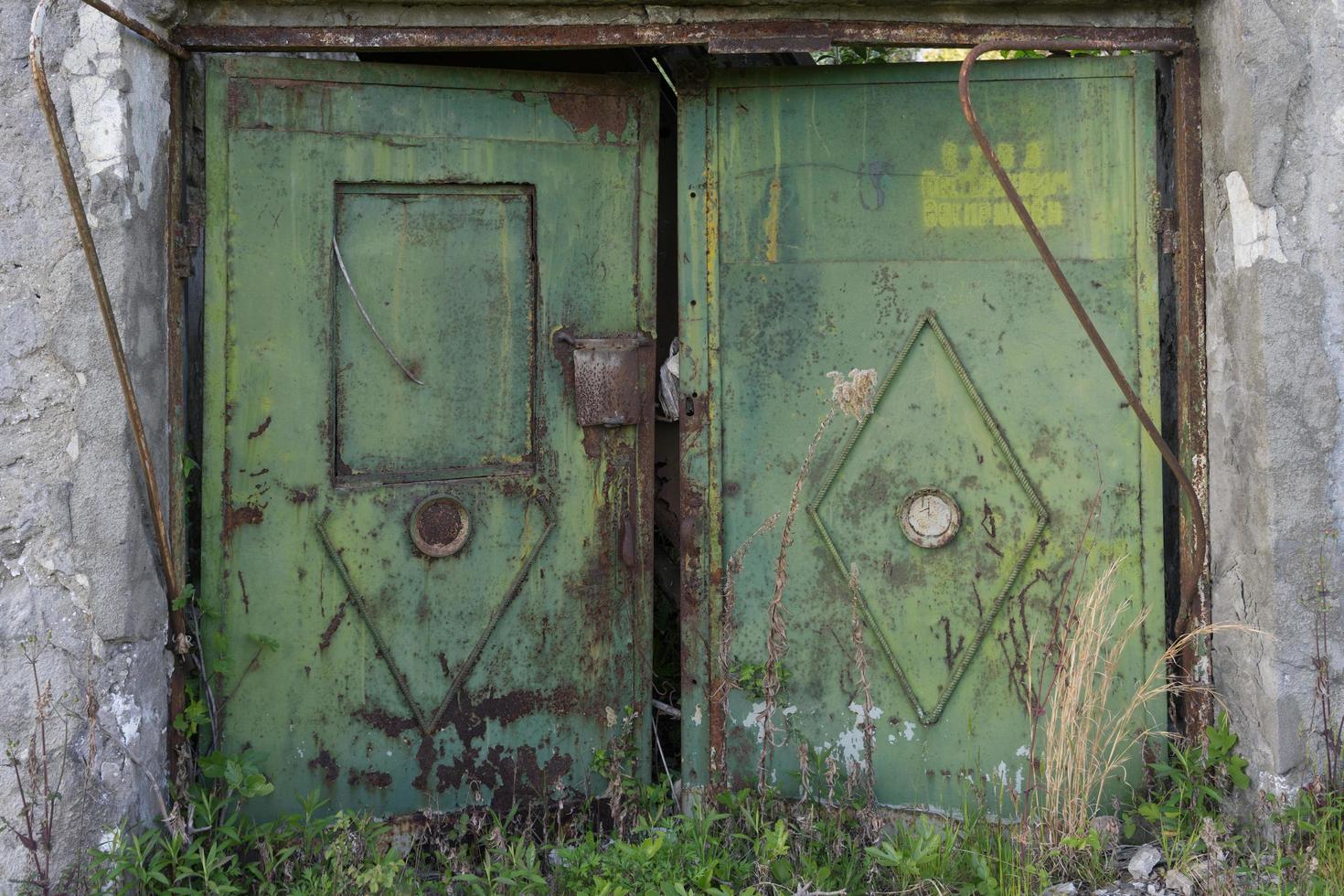 ancienne porte métallique sur le fond d'un mur de briques grises. photo