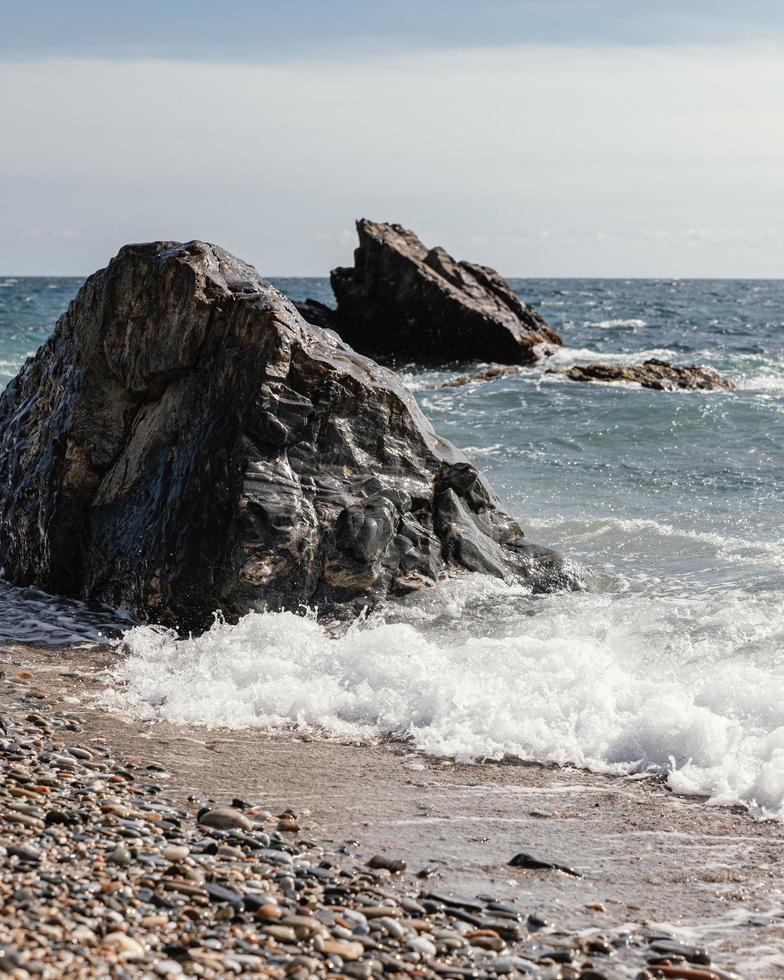 vagues et gros rochers sur la plage photo