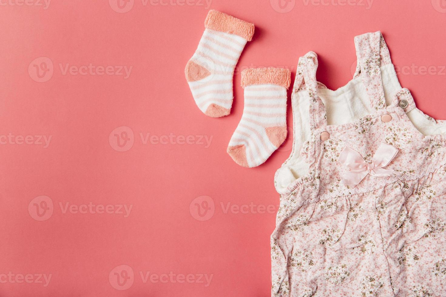 Paire de chaussettes bébé et robe sur fond de couleur vive photo