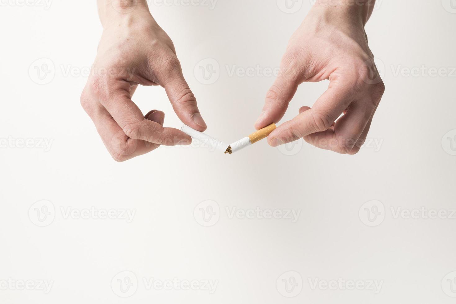 La main de la personne casser une cigarette sur fond blanc photo