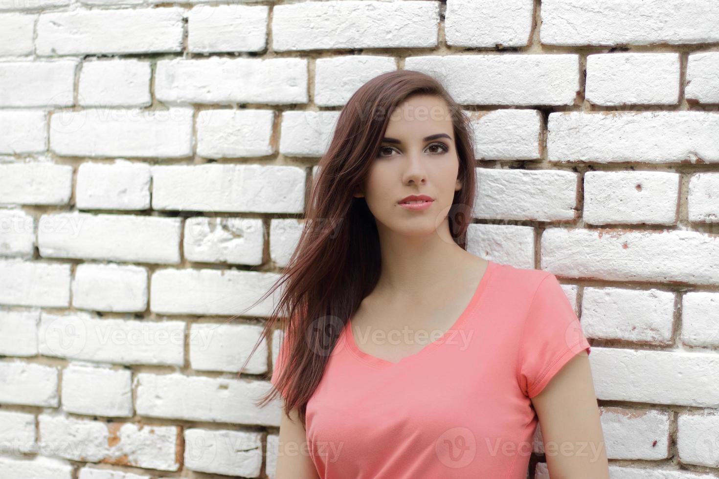 femme contre un mur de briques blanches photo