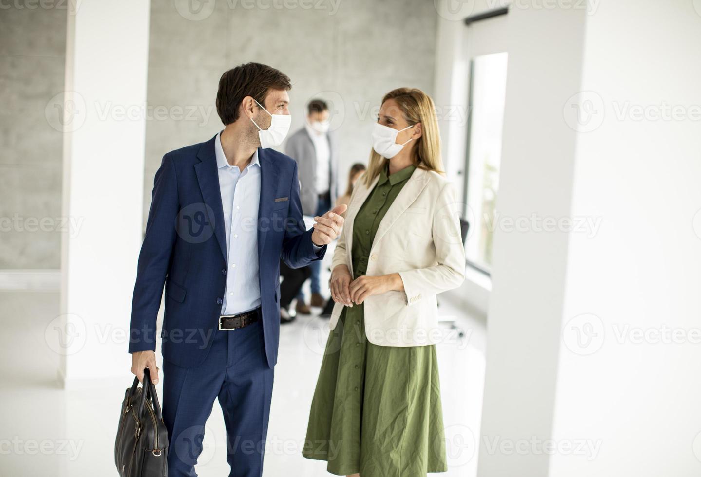 deux professionnels masqués marchant dans un bureau photo