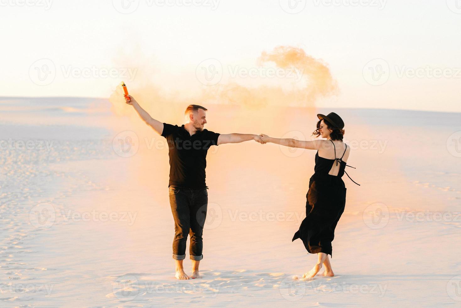 mec et une fille en vêtements noirs étreignent et courent sur le sable blanc avec de la fumée orange photo