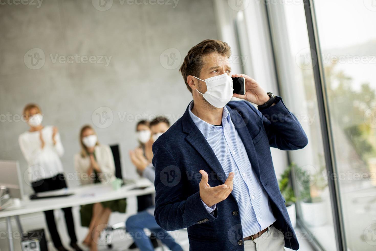 homme masqué au téléphone au bureau photo
