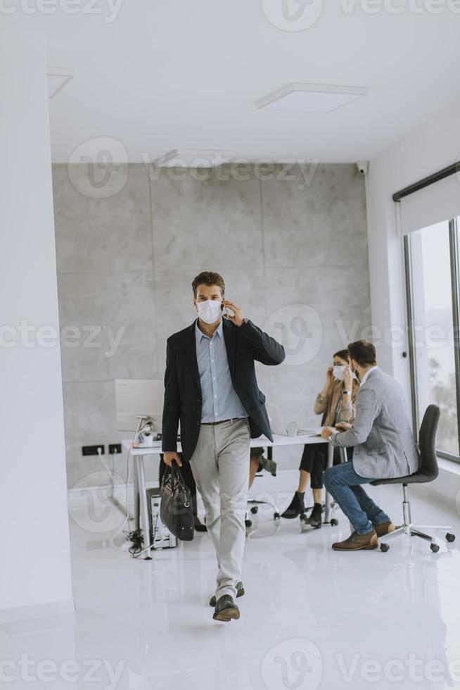homme d & # 39; affaires masqué prenant le téléphone et marchant photo