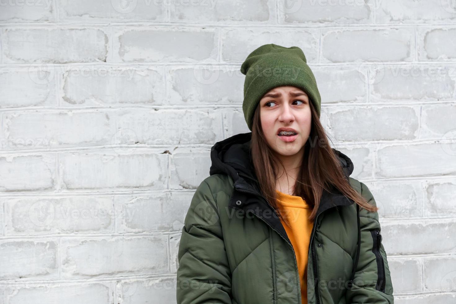 Portrait d'une belle fille incrédule avec des accolades dans un pull jaune et un chapeau kaki qui se tient près d'un mur de briques blanches photo
