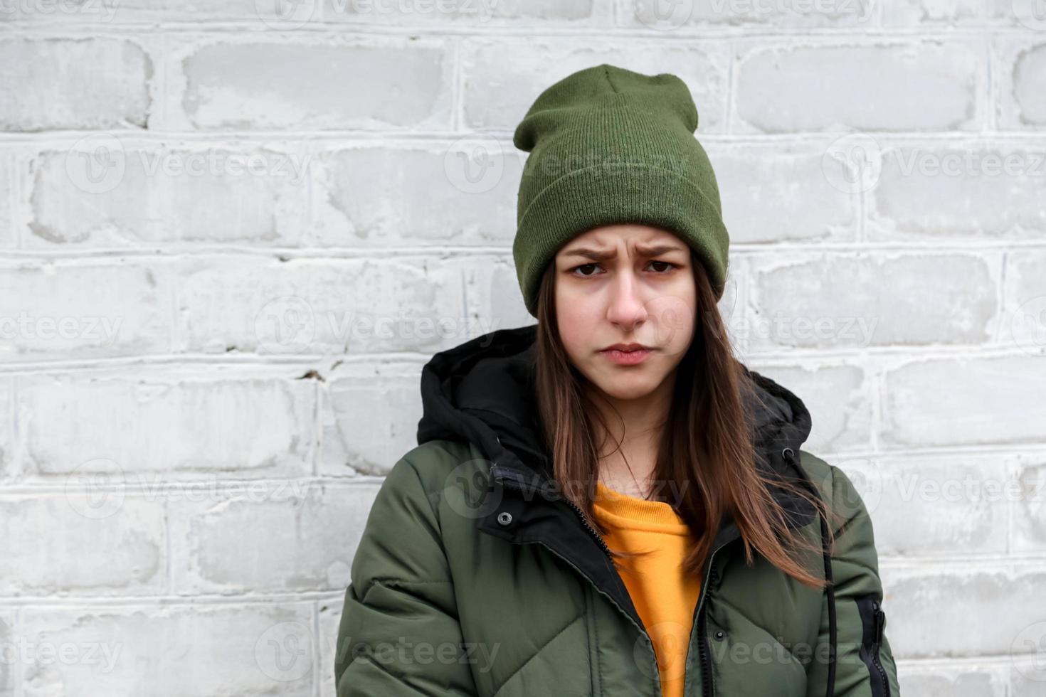 Portrait d'une belle fille triste dans un pull jaune et un chapeau kaki photo